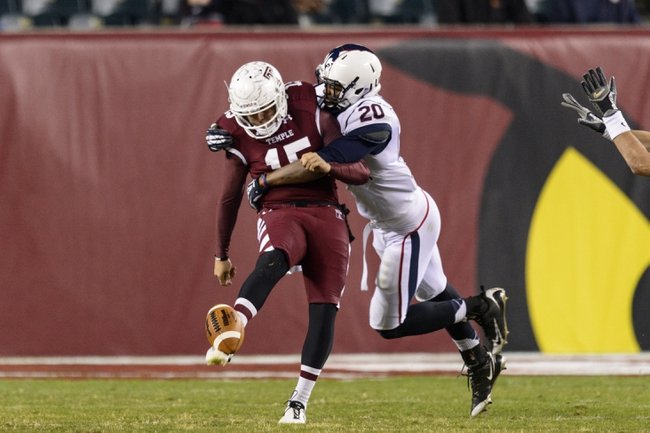 Nov 23, 2013; Philadelphia, PA, USA; Temple Owls punter Paul Layton (15) gets hit by Connecticut Huskies safety Obi Melifonwu (20) as he gets off the punt during the fourth quarter at Lincoln Financial Field. UCONN defeated Temple 28-21. Mandatory Credit: Howard Smith-USA TODAY Sports