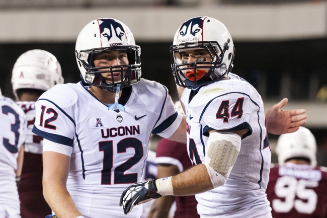 Nov 23, 2013; Philadelphia, PA, USA; Connecticut Huskies running back Max DeLorenzo (44) celebrates scoring a touchdown with quarterback Casey Cochran (12) during the third quarter against the Temple Owls at Lincoln Financial Field. UCONN defeated Temple 28-21. Mandatory Credit: Howard Smith-USA TODAY Sports