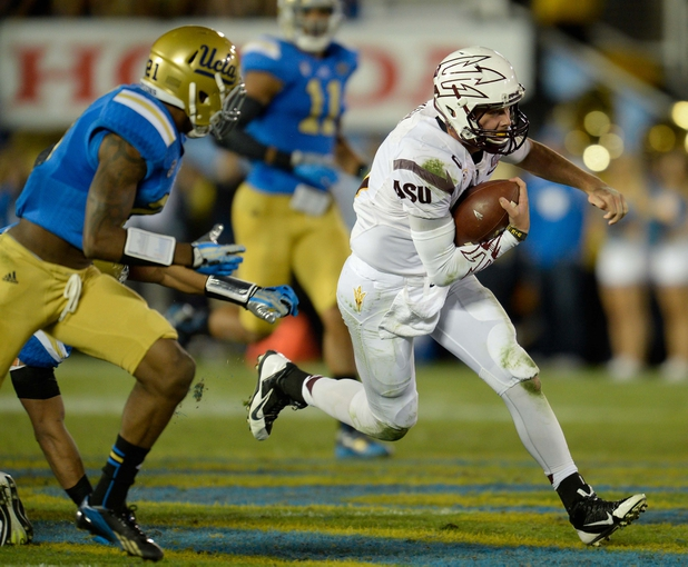 Nov 23, 2013; Pasadena, CA, USA; Arizona State Sun Devils quarterback Taylor Kelly (10) runs past UCLA Bruins safety Tahaan Goodman during second quarter action on the Sun Devils 38-33 win at Rose Bowl. Mandatory Credit: Robert Hanashiro-USA TODAY Sports
