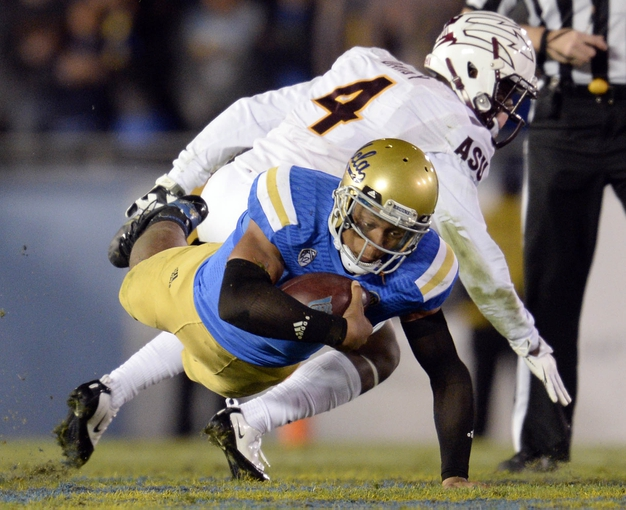 Nov 23, 2013; Pasadena, CA, USA; UCLA Bruins quarterback Brett Hundley (17) dives for extra yards past Arizona State Sun Devils safety Alden Darby (4) during the second half at Rose Bowl. Mandatory Credit: Robert Hanashiro-USA TODAY Sports