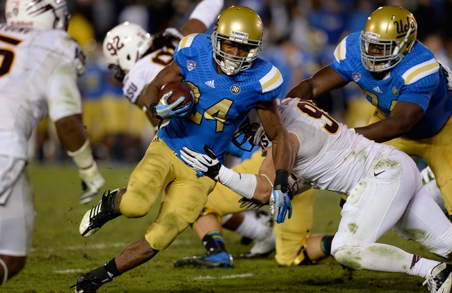 Nov 23, 2013; Pasadena, CA, USA; UCLA Bruins running back Paul Perkins (24) tries to run past Arizona State Sun Devils defensive end Gannon Conway (95) during second half action at Rose Bowl. Mandatory Credit: Robert Hanashiro-USA TODAY Sports