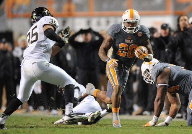 Nov 23, 2013; Knoxville, TN, USA; Tennessee Volunteers running back Rajion Neal (20) runs the ball against Vanderbilt Commodores linebacker Darreon Herring (35) at Neyland Stadium. Vanderbilt won 14 to 10. Mandatory Credit: Randy Sartin-USA TODAY Sports