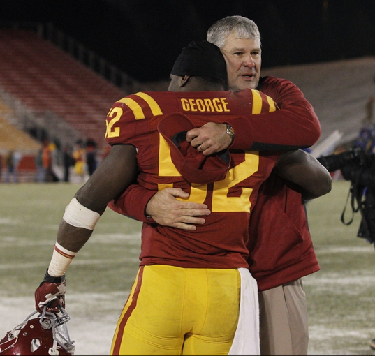 Nov 23, 2013; Ames, IA, USA; Iowa State Cyclones head coach Paul Rhoads hugs linebacker Jeremiah George (52) after defeating the Kansas Jayhawks at Jack Trice Stadium. Iowa State won 34-0. Mandatory Credit: Bruce Thorson-USA TODAY Sports