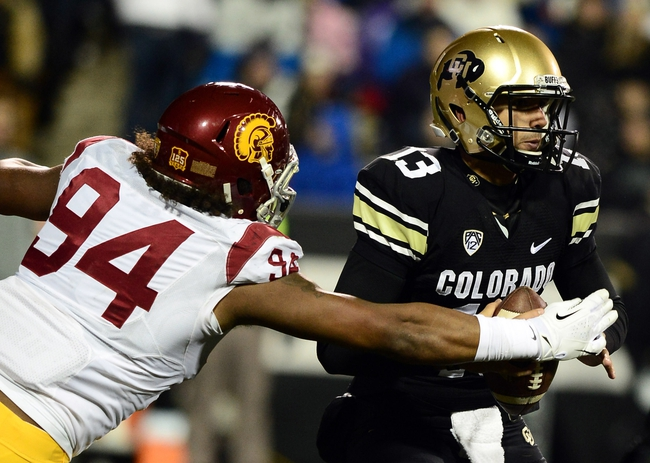 Nov 23, 2013; Boulder, CO, USA; Southern California Trojans defensive end Leonard Williams (94) reaches for the ball held by Colorado Buffaloes quarterback Sefo Liufau (13) in the second quarter at Folsom Field. Mandatory Credit: Ron Chenoy-USA TODAY Sports