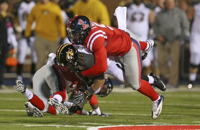 Nov 23, 2013; Oxford, MS, USA; Missouri Tigers running back Russell Hansbrough (32) carries the ball and is tackled by Mississippi Rebels defensive end Robert Nkemdiche (5) during the game at Vaught-Hemingway Stadium. Missouri Tigers defeat the Mississippi Rebels 24-10.  Mandatory Credit: Spruce Derden-USA TODAY Sports