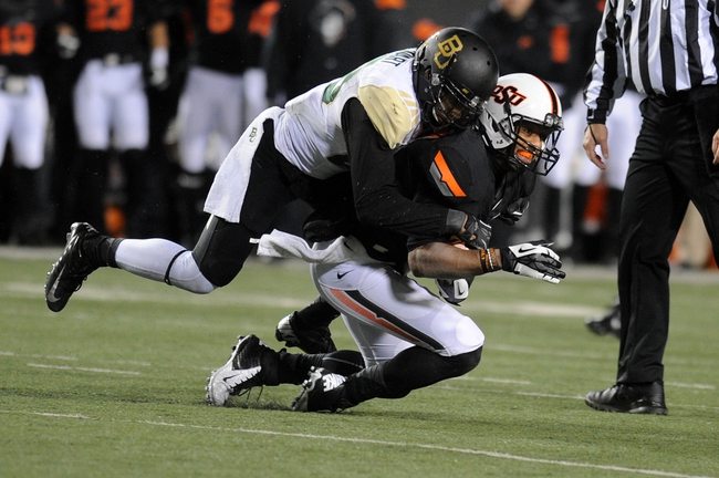 Nov 23, 2013; Stillwater, OK, USA;  Oklahoma State Cowboys wide receiver Tracy Moore (87) is tackled by Baylor Bears safety Orion Stewart (28) at Boone Pickens Stadium. Mandatory Credit: Mark D. Smith-USA TODAY Sports