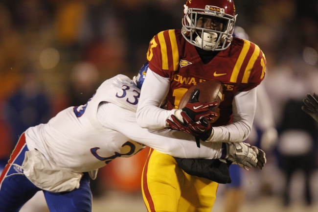 Nov 23, 2013; Ames, IA, USA; Iowa State Cyclones receiver Dondre Daley (13) catches the pass and is  tackled by Kansas Jayhawks defender Cassius Sendish (33) in the third quarter at Jack Trice Stadium. Iowa State won 34-0. Mandatory Credit: Bruce Thorson-USA TODAY Sports