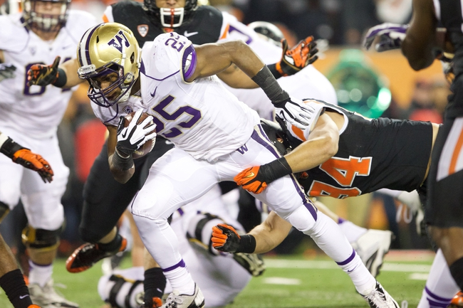 Nov 23, 2013; Corvallis, OR, USA; Washington Huskies running back Bishop Sankey (25) breaks a tackle from Oregon State Beavers defensive end Devon Kell (94) for a touchdown in the first half at Reser Stadium. Mandatory Credit: Jaime Valdez-USA TODAY Sports