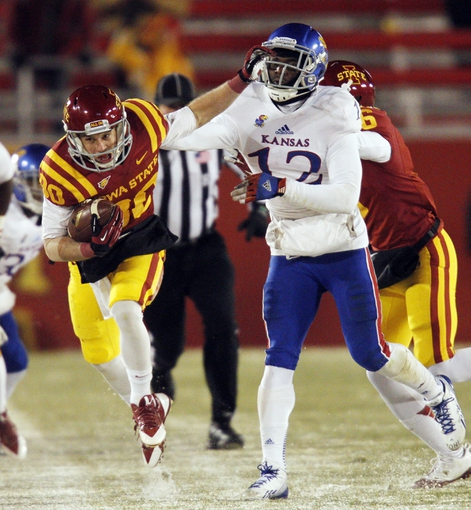 Nov 23, 2013; Ames, IA, USA; Iowa State Cyclones receiver Justin Coleman (80) catches a pass against Kansas Jayhawks defender Dexter McDonald (12) in the third quarter at Jack Trice Stadium. Iowa State won 34-0. Mandatory Credit: Bruce Thorson-USA TODAY Sports