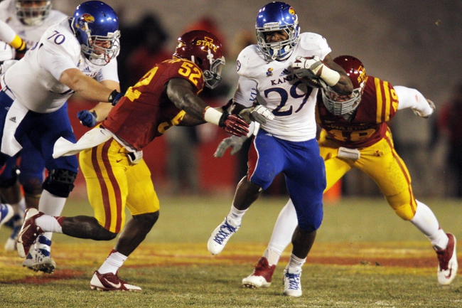 Nov 23, 2013; Ames, IA, USA; Iowa State Cyclones defender Jeremiah George (52) tackles Kansas Jayhawks running back James Sims (29) in the first quarter at Jack Trice Stadium. Iowa State won 34-0. Mandatory Credit: Bruce Thorson-USA TODAY Sports