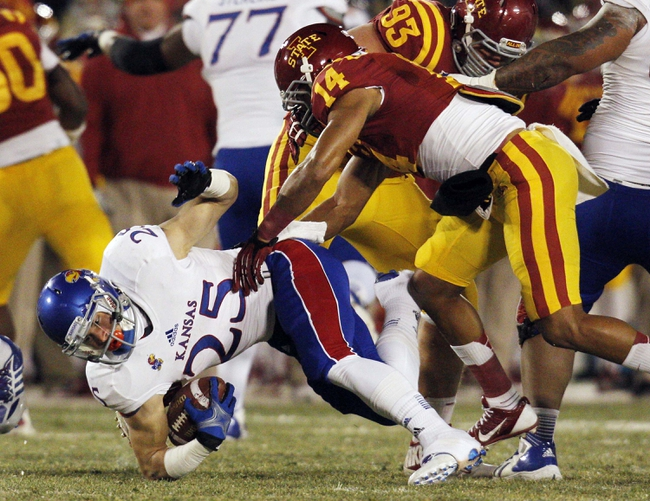 Nov 23, 2013; Ames, IA, USA; Iowa State Cyclones defender Jared Brackens (14) tackles Kansas Jayhawks running back Brandon Bourbon (25) in the first quarter at Jack Trice Stadium. Iowa State won 34-0. Mandatory Credit: Bruce Thorson-USA TODAY Sports