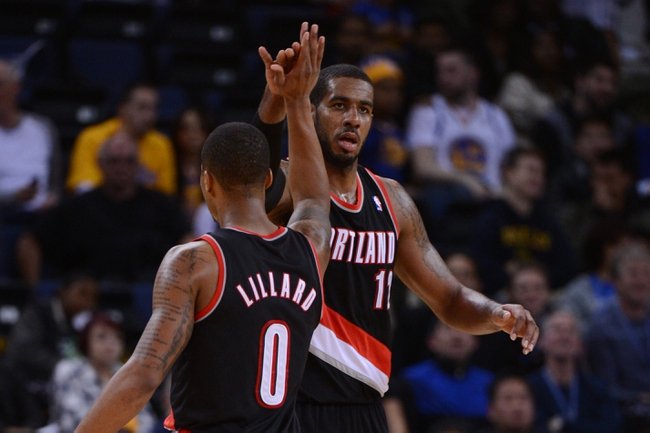 November 23, 2013; Oakland, CA, USA; Portland Trail Blazers power forward LaMarcus Aldridge (12, right) celebrates with point guard Damian Lillard (0) against the Golden State Warriors during the fourth quarter at Oracle Arena. The Trail Blazers defeated the Warriors 113-101. Mandatory Credit: Kyle Terada-USA TODAY Sports