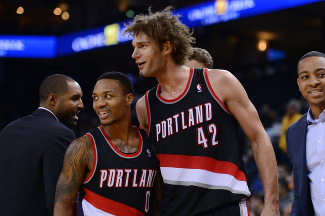 November 23, 2013; Oakland, CA, USA; Portland Trail Blazers point guard Damian Lillard (0) and center Robin Lopez (42) celebrate against the Golden State Warriors during the fourth quarter at Oracle Arena. The Trail Blazers defeated the Warriors 113-101. Mandatory Credit: Kyle Terada-USA TODAY Sports