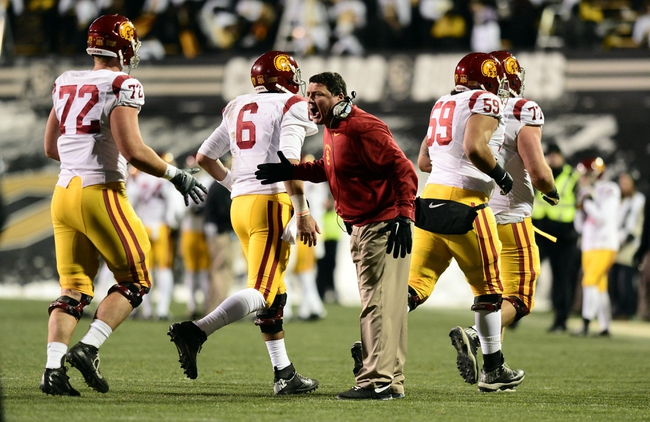 Nov 23, 2013; Boulder, CO, USA; Southern California Trojans interim head coach Ed Orgeron congratulates offensive tackle Chad Wheeler (72) and quarterback Cody Kessler (6) and guard John Martinez (59) and and offensive tackle Kevin Graf (77) after a touchdown drive in the second quarter against the Colorado Buffaloes at Folsom Field. Mandatory Credit: Ron Chenoy-USA TODAY Sports