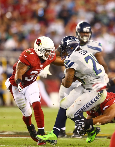 Oct 17, 2013; Phoenix, AZ, USA; Seattle Seahawks running back Marshawn Lynch (24) is tackled by Arizona Cardinals safety Yeremiah Bell (37) at University of Phoenix Stadium. Mandatory Credit: Mark J. Rebilas-USA TODAY Sports
