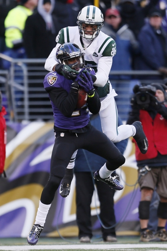 Nov 24, 2013; Baltimore, MD, USA; Baltimore Ravens cornerback Corey Graham (24) leaps to make an interception in front of New York Jets wide receiver David Nelson (86) at M&T Bank Stadium. Mandatory Credit: Mitch Stringer-USA TODAY Sports