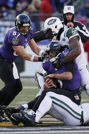 Nov 24, 2013; Baltimore, MD, USA; Baltimore Ravens quarterback Joe Flacco (5) is sacked by New York Jets cornerback Darrin Walls (30) at M&T Bank Stadium. Mandatory Credit: Mitch Stringer-USA TODAY Sports