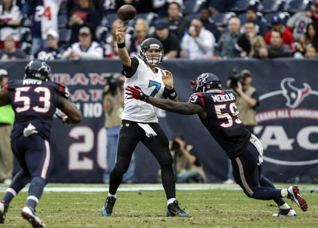 Nov 24, 2013; Houston, TX, USA; Jacksonville Jaguars quarterback Chad Henne (7) attempts a pass during the fourth quarter as Houston Texans outside linebacker Whitney Mercilus (59) applies pressure at Reliant Stadium. The Jaguars defeated the Texans 13-6. Mandatory Credit: Troy Taormina-USA TODAY Sports