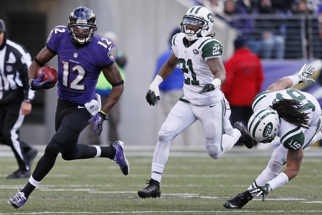 Nov 24, 2013; Baltimore, MD, USA; Baltimore Ravens kick returner Jacoby Jones (12) runs with the ball past New York Jets defenders Ellis Lankster (21) and Josh Cribbs (16) at M&T Bank Stadium. Mandatory Credit: Mitch Stringer-USA TODAY Sports
