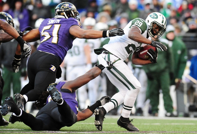 Nov 24, 2013; Baltimore, MD, USA; New York Jets running back Bilal Powell (29) runs with the ball as Baltimore Ravens linebacker Daryl Smith (51) and linebacker Pernell McPhee (90) tackle at M&T Bank Stadium. The Ravens won 19-3. Mandatory Credit: Evan Habeeb-USA TODAY Sports