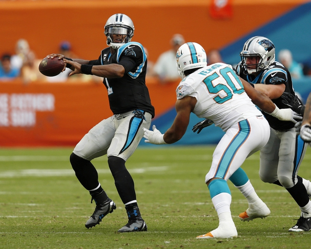 Nov 24, 2013; Miami Gardens, FL, USA; Carolina Panthers quarterback Cam Newton (1) drops back to pass as Miami Dolphins defensive end Olivier Vernon (50) rushes in the second half of a game at Sun Life Stadium. The Panthers won 20-16. Mandatory Credit: Robert Mayer-USA TODAY Sports