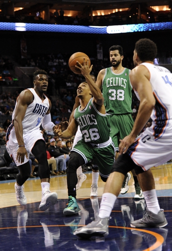 Nov 25, 2013; Charlotte, NC, USA; Boston Celtics guard Phil Pressey (26) drives to the basket as he is defended by Charlotte Bobcats forward Jeff Adrien (4) and forward Jeffery Taylor (44) during the first half of the game at Time Warner Cable Arena. Mandatory Credit: Sam Sharpe-USA TODAY Sports