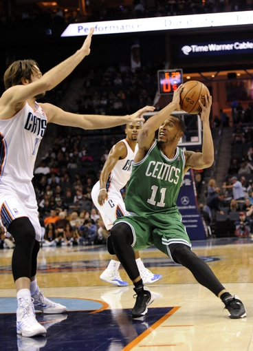 Nov 25, 2013; Charlotte, NC, USA; Boston Celtics guard Courtney Lee (11) prepares to take a shot as he is defended by Charlotte Bobcats forward Josh McRoberts (11) during the first half of the game at Time Warner Cable Arena. Mandatory Credit: Sam Sharpe-USA TODAY Sports