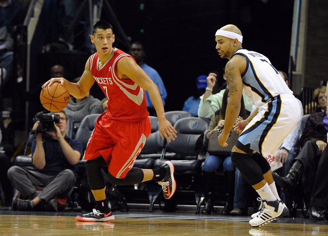 Nov 25, 2013; Memphis, TN, USA; Houston Rockets point guard Jeremy Lin (7) drives against Memphis Grizzlies point guard Jerryd Bayless (7) during the first quarter at FedExForum. Mandatory Credit: Justin Ford-USA TODAY Sports