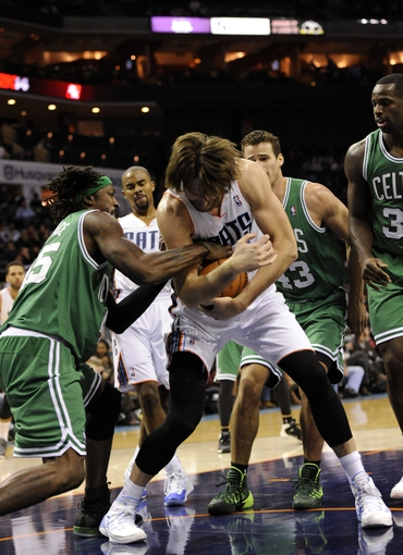 Nov 25, 2013; Charlotte, NC, USA; Charlotte Bobcats forward Josh McRoberts (11) and Boston Celtics forward Gerald Wallace (45) fight for the ball during the second half of the game at Time Warner Cable Arena. Celtics win 96-86. Mandatory Credit: Sam Sharpe-USA TODAY Sports