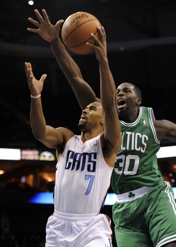 Nov 25, 2013; Charlotte, NC, USA; Charlotte Bobcats guard Ramon Sessions (7) drives to the basket as he is defended by Boston Celtics forward Brandon Bass (30) during the second half of the game at Time Warner Cable Arena. Celtics win 96-86. Mandatory Credit: Sam Sharpe-USA TODAY Sports