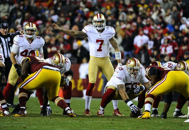 Nov 25, 2013; Landover, MD, USA; San Francisco 49ers quarterback Colin Kaepernick (7) looks over the Washington Redskins defense during the second half at FedEx Field. The 49ers won 27-6. Mandatory Credit: Brad Mills-USA TODAY Sports