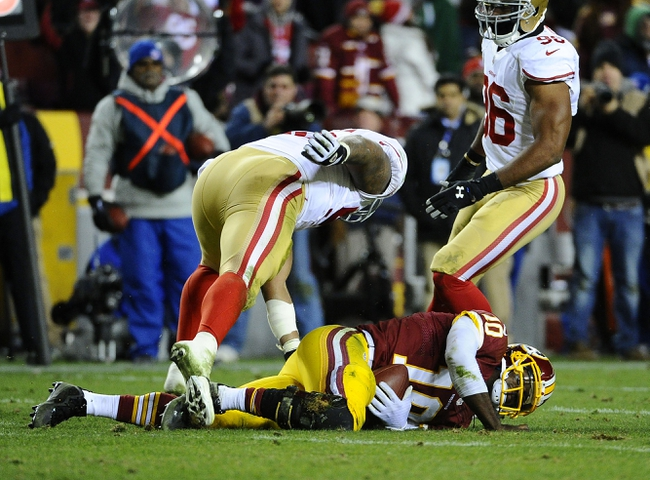 Nov 25, 2013; Landover, MD, USA; Washington Redskins quarterback Robert Griffin III (10) is sacked by San Francisco 49ers linebacker Corey Lemonier (96) and linebacker Ahmad Brooks (left) during the second half at FedEx Field. The 49ers won 27-6. Mandatory Credit: Brad Mills-USA TODAY Sports