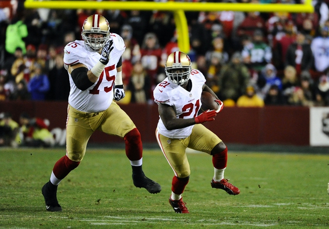 Nov 25, 2013; Landover, MD, USA; San Francisco 49ers running back Frank Gore (21) rushes the ball as guard Alex Boone (75) prepares to block against the Washington Redskins during the second half at FedEx Field. The 49ers won 27-6. Mandatory Credit: Brad Mills-USA TODAY Sports