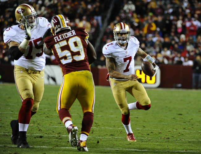 Nov 25, 2013; Landover, MD, USA; San Francisco 49ers quarterback Colin Kaepernick (7) rushes the ball as Washington Redskins linebacker London Fletcher (59) defends during the second half at FedEx Field. The 49ers won 27-6. Mandatory Credit: Brad Mills-USA TODAY Sports