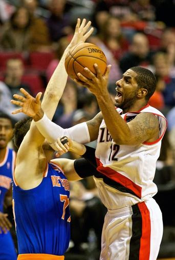 Nov 25, 2013; Portland, OR, USA; Portland Trail Blazers power forward LaMarcus Aldridge (12) shoots over New York Knicks power forward Andrea Bargnani (77) at the Moda Center. Mandatory Credit: Craig Mitchelldyer-USA TODAY Sports