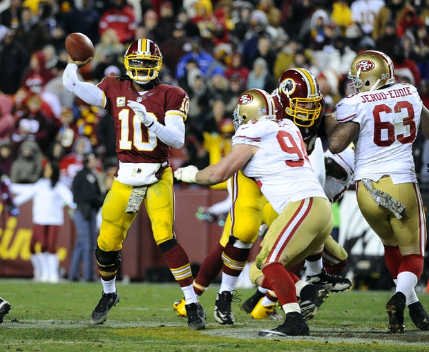 Nov 25, 2013; Landover, MD, USA; Washington Redskins quarterback Robert Griffin III (10) throws a pass as San Francisco 49ers defensive tackle Justin Smith (94) rushes during the second half at FedEx Field. The 49ers won 27-6. Mandatory Credit: Brad Mills-USA TODAY Sports