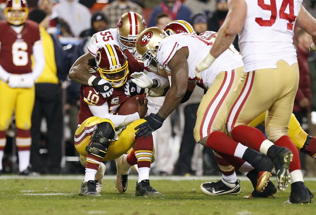 Nov 25, 2013; Landover, MD, USA; Washington Redskins quarterback Robert Griffin III (10) is sacked by San Francisco 49ers outside linebacker Ahmad Brooks (55) and 49ers tight end Demarcus Dobbs (83) in the third quarter at FedEx Field. The 49ers won 27-6. Mandatory Credit: Geoff Burke-USA TODAY Sports