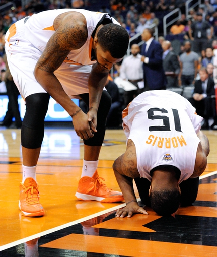 Nov 10, 2013; Phoenix, AZ, USA; Phoenix Suns power forward Markieff Morris (11) checks to see if power forward Marcus Morris (15) is ok during the second quarter against the New Orleans Pelicans at US Airways Center. The Suns beat the Pelicans 101-94. Mandatory Credit: Casey Sapio-USA TODAY Sports