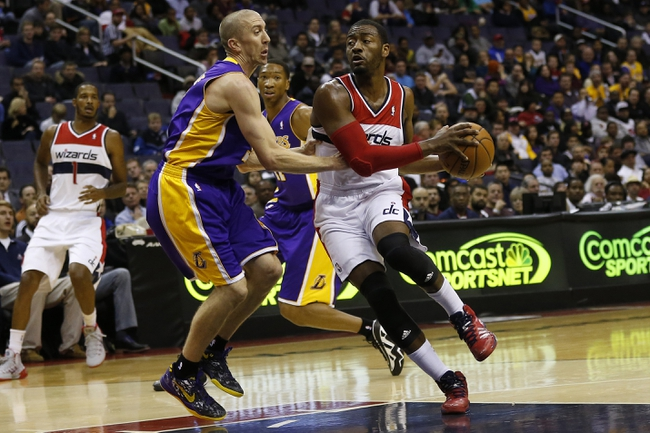 Nov 26, 2013; Washington, DC, USA; Washington Wizards point guard John Wall (2) dribbles the ball as Los Angeles Lakers point guard Steve Blake (5) defends in the first quarter at Verizon Center. Mandatory Credit: Geoff Burke-USA TODAY Sports