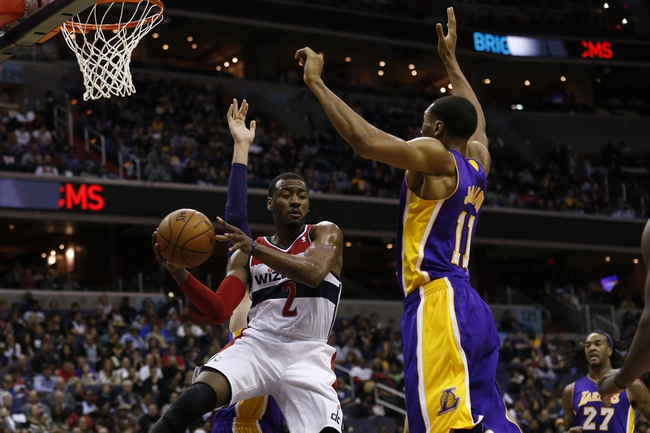 Nov 26, 2013; Washington, DC, USA; Washington Wizards point guard John Wall (2) passes the ball around Los Angeles Lakers shooting guard Wesley Johnson (11) in the second quarter at Verizon Center. Mandatory Credit: Geoff Burke-USA TODAY Sports