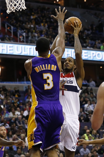 Nov 26, 2013; Washington, DC, USA; Washington Wizards small forward Trevor Ariza (1) shoots the ball as Los Angeles Lakers power forward Shawne Williams (3) defends in the second quarter at Verizon Center. The Wizards won 116-111. Mandatory Credit: Geoff Burke-USA TODAY Sports