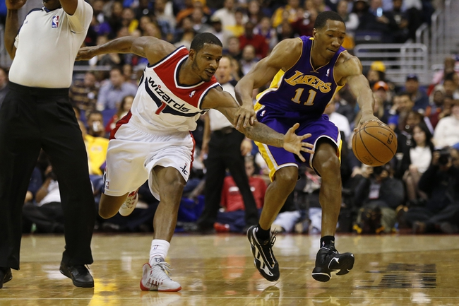 Nov 26, 2013; Washington, DC, USA; Washington Wizards small forward Trevor Ariza (1) and Los Angeles Lakers shooting guard Wesley Johnson (11) battle for the ball in the second quarter at Verizon Center. The Wizards won 116-111. Mandatory Credit: Geoff Burke-USA TODAY Sports