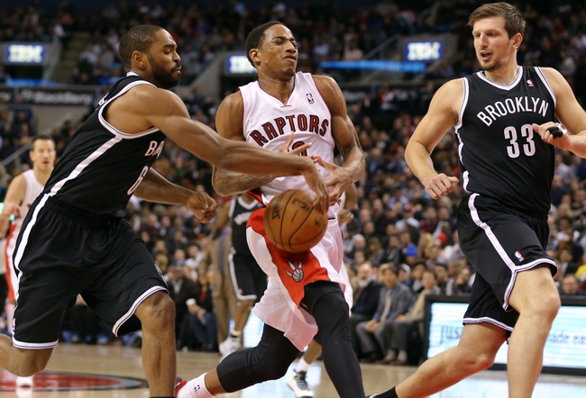 Nov 26, 2013; Toronto, Ontario, CAN; Toronto Raptors guard DeMar DeRozan (10) has the ball stripped from him by Brooklyn Nets forward Alan Anderson (6) at Air Canada Centre. The Nets beat the Raptors 102-100. Mandatory Credit: Tom Szczerbowski-USA TODAY Sports