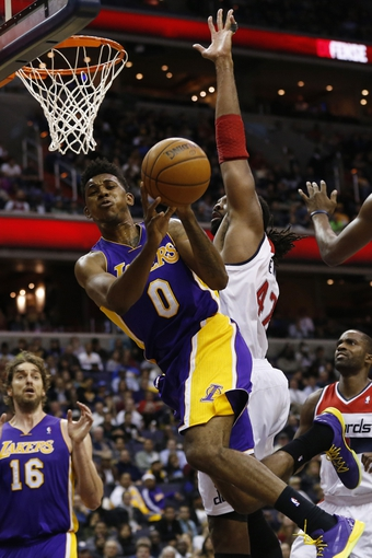 Nov 26, 2013; Washington, DC, USA; Los Angeles Lakers small forward Nick Young (0) shoots the ball as Washington Wizards power forward Nene Hilario (42) defends in the fourth quarter at Verizon Center. The Wizards won 116-111. Mandatory Credit: Geoff Burke-USA TODAY Sports