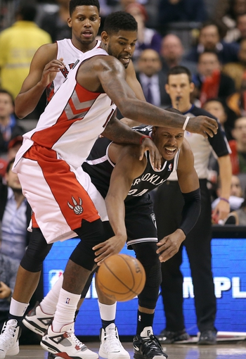 Nov 26, 2013; Toronto, Ontario, CAN; Brooklyn Nets forward Paul Pierce (34) passes the ball under pressure from Toronto Raptors center Amir Johnson (15) at Air Canada Centre. The Nets beat the Raptors 102-100. Mandatory Credit: Tom Szczerbowski-USA TODAY Sports
