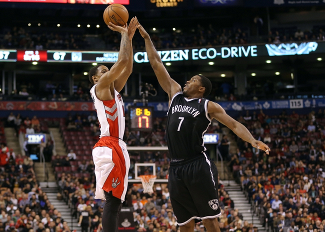 Nov 26, 2013; Toronto, Ontario, CAN; Toronto Raptors guard DeMar DeRozan (10) is fouled by Brooklyn Nets guard Joe Johnson (7) as he goes up to shoot at Air Canada Centre. The Nets beat the Raptors 102-100. Mandatory Credit: Tom Szczerbowski-USA TODAY Sports