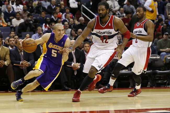 Nov 26, 2013; Washington, DC, USA; Los Angeles Lakers point guard Steve Blake (5) dribbles the ball past Washington Wizards power forward Nene Hilario (42) in the third quarter at Verizon Center. The Wizards won 116-111. Mandatory Credit: Geoff Burke-USA TODAY Sports