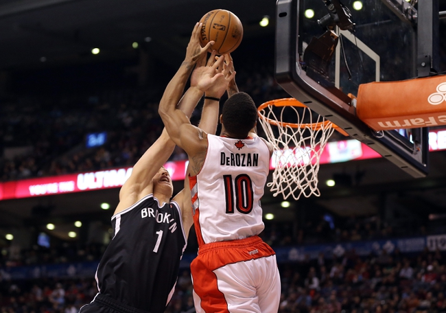 Nov 26, 2013; Toronto, Ontario, CAN; Toronto Raptors guard DeMar DeRozan (10) is blocked by Brooklyn Nets forward Mason Plumlee (1) at Air Canada Centre. The Nets beat the Raptors 102-100. Mandatory Credit: Tom Szczerbowski-USA TODAY Sports