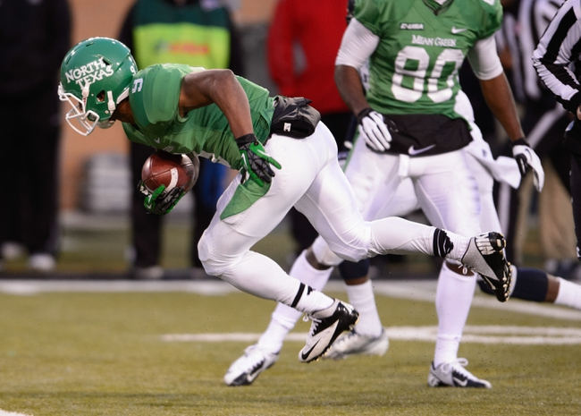 Nov 23, 2013; Denton, TX, USA; North Texas Mean Green wide receiver Carlos Harris (9) stretches for a first down against the UTSA Roadrunners during the game at Apogee Stadium. The Roadrunners defeated the Mean Green 21-13. Mandatory Credit: Jerome Miron-USA TODAY Sports