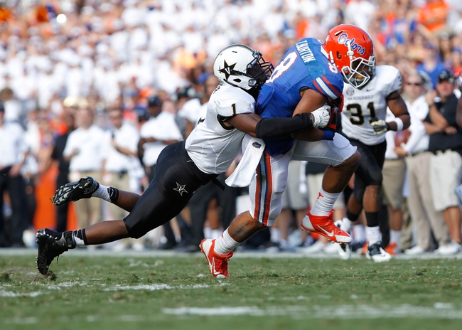 Nov 9, 2013; Gainesville, FL, USA; Florida Gators wide receiver Trey Burton (8) runs with the ball as Vanderbilt Commodores safety Kenny Ladler (1) attempted to defend during the second half at Ben Hill Griffin Stadium. Vanderbilt Commodores defeated the Florida Gators 34-17. Mandatory Credit: Kim Klement-USA TODAY Sports